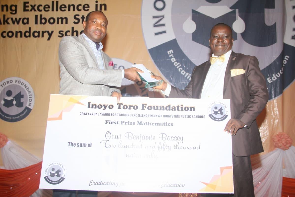 Mr Aniekan Willie presenting the award to the 1st prize winner Mathematics, Onwi Benjamin Bassey