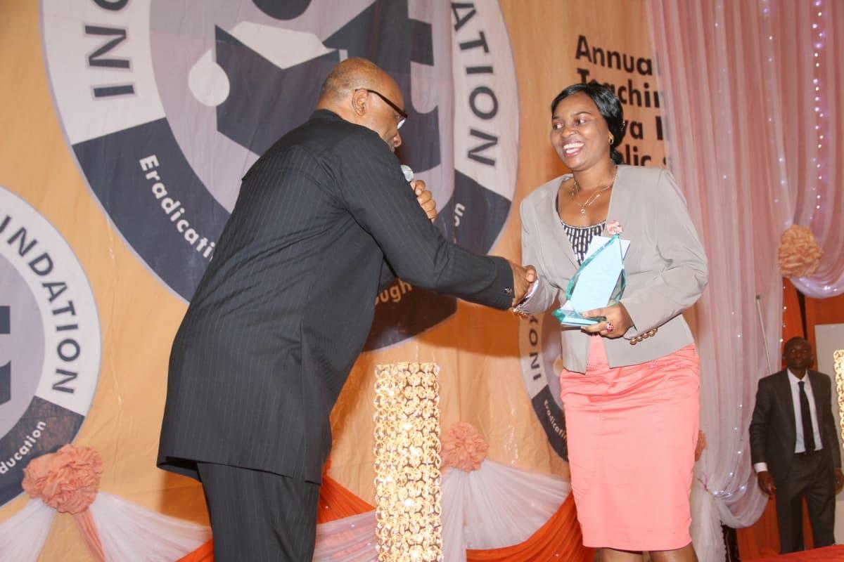 Mr Boni Akpan presenting the award to a representative of the 2nd prize winner in English Language, Mr Stephen Abia