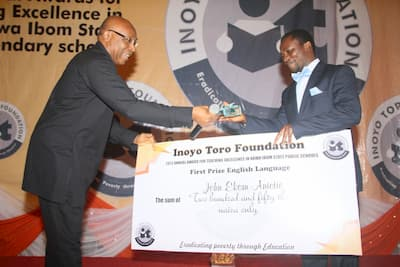 Mr Boni Akpan presenting the award to the 1st prize winner English Language, John Ekom Anietie