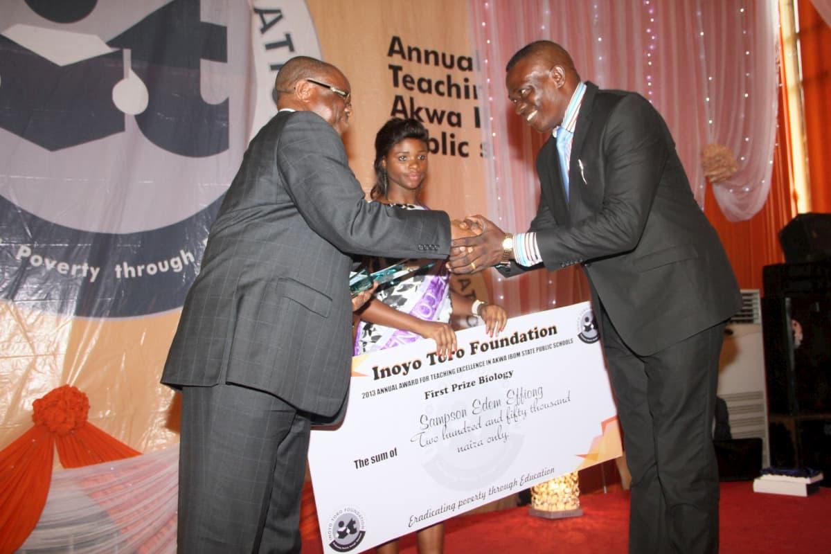Mr Emeka Obi (L) of Addax Petroleum presenting the award to the 1st prize in Biology Sampson Edem Effiong