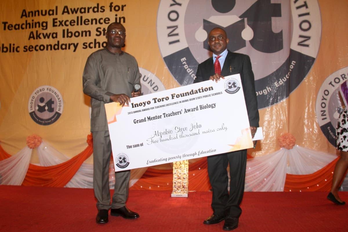 Mr Paul Arinze of Exxonmobil (L) presenting the award to the Grand Mentor Award winner Biology, Akpabio Steve John
