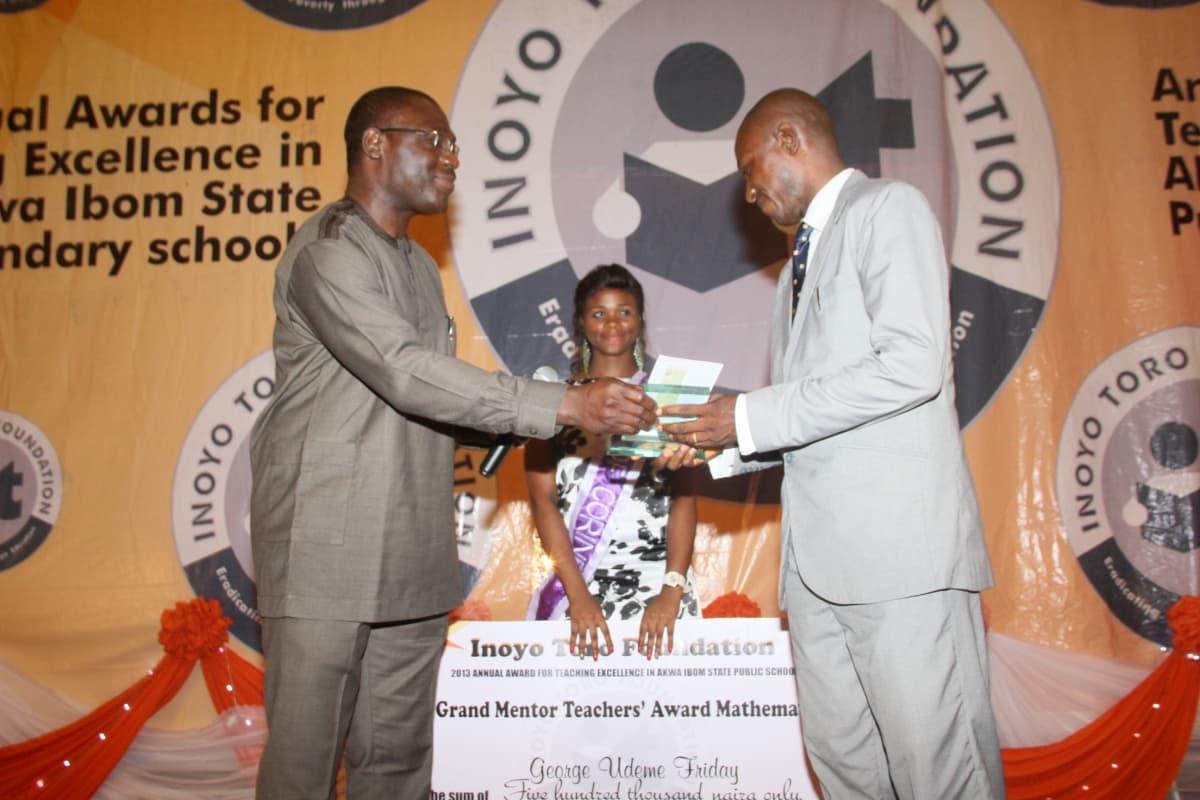 Mr Paul Arinze of Exxonmobil (L) presenting the award to the Grand Mentor Award winner Mathematics, George Udeme Friday