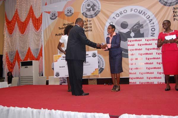 Dr Ini Urua (L) presenting the award to the 1st prize winner Biology, Eno Ernest Okokon