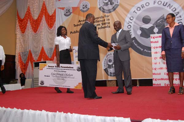 Dr Ini Urua (L) presenting the award to the 2nd prize winner Biology, Noah Cyril Noah