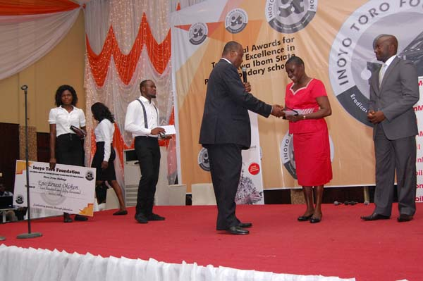 Dr Ini Urua (L) presenting the award to the 3rd prize winner Biology, Glory Okon Abia