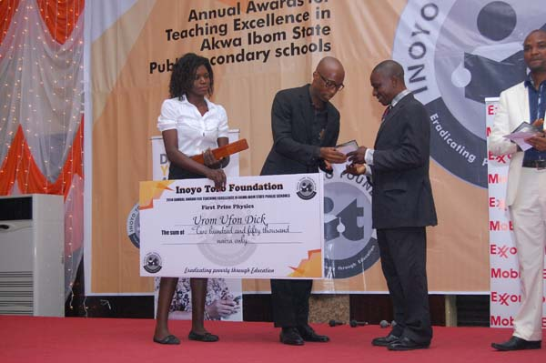 Honourable Onofiok Luke (C) presenting the award to the 1st prize winner Physics, Ufon Dick Urom