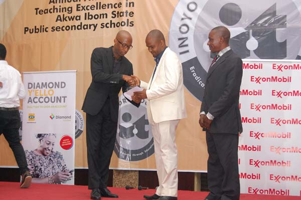 Honourable Onofiok Luke (L) presenting the award to the 2nd prize winner Physics, Mfon David Umoh