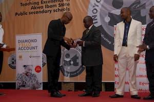 Honourable Onofiok Luke (L) presenting the award to the 3rd prize winner Physics, Emem Udo Ubom