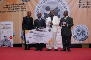 Honourable Onofiok Luke (r) with the winners in the Physics Category sponsored by Delta Afrik Charitable Foundation