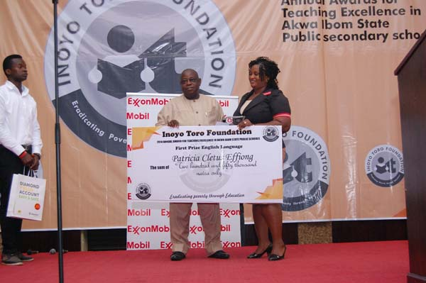 Mr E. T. Abraham presenting the award on behalf of the sponsor, Mr Boni Akpan to the 1st prize winner, English Language, Patricia Cletus Effiong