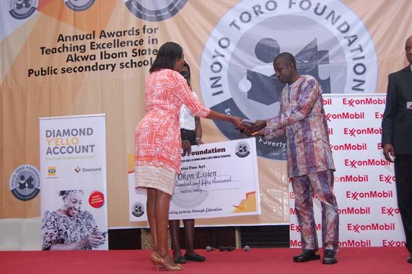 Mrs Iyabo Akai (L) presenting the award to the 1st prize winner Fine Arts, Mfon Okon Essien