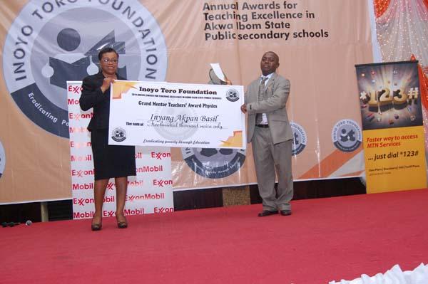 Mrs Rita Umoren presenting the award to the Grand Mentor Award winner Physics, Mr Inyang Akpan Basil