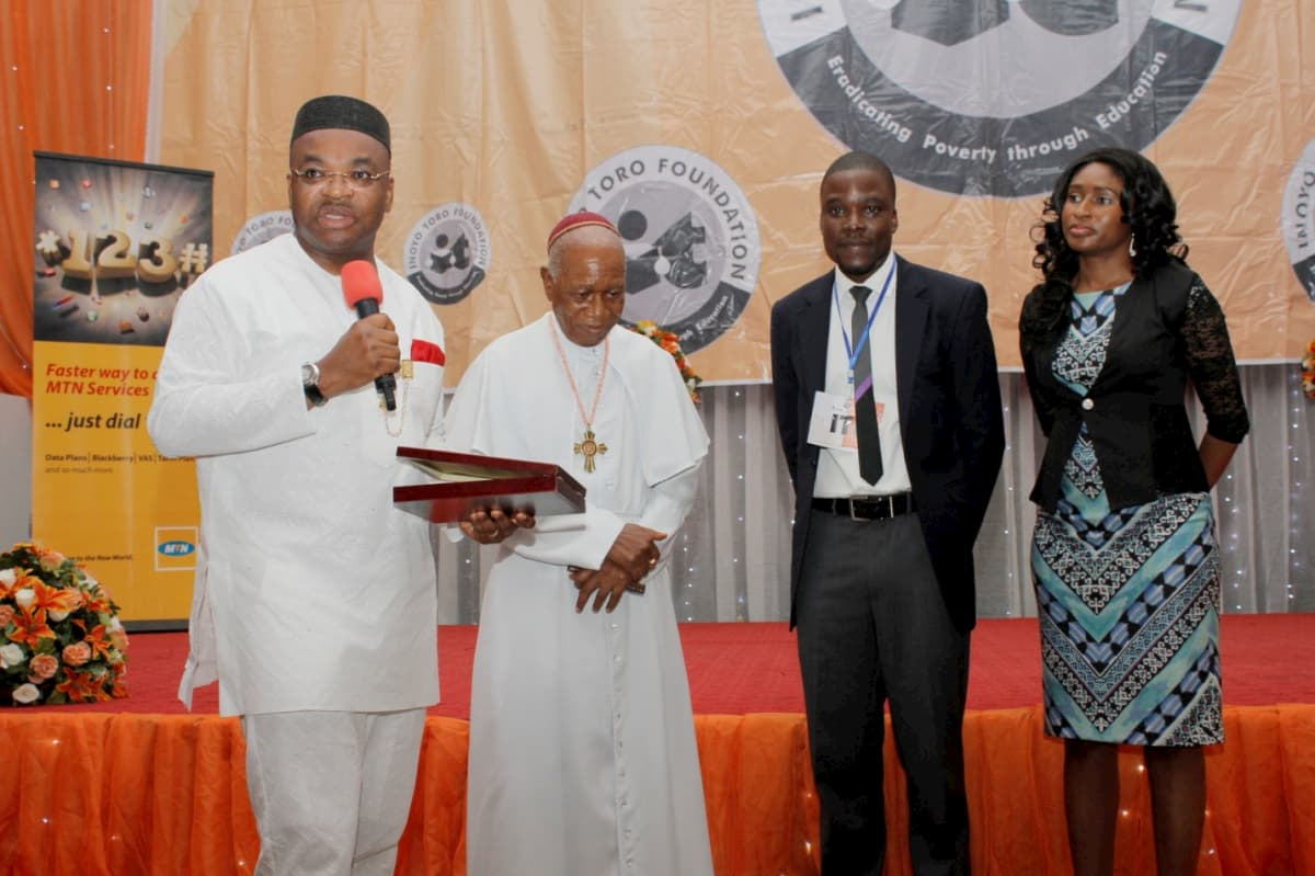 Akwa Ibom State Governor, Udom Emmanuel (1st From Left) And Prelate Emeritus Sunday Mbang (2nd From Left) presenting a Plaque to Pioneer Program Manager, Idorenyin Mbang And Wife for His Meritorious Service to The Foundation.