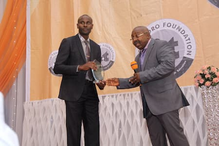 MR GABRIEL ETIM 3RD POSITION PHYSICS RECEIVING HIS AWARD FROM ARCH IME EKPO