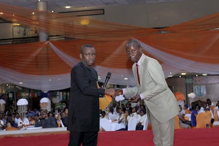 DR GEORGE AKPAN PRESENTING AN AWARD ON BEHALF OF THE SPONSORS DELTA AFRIK TO THE 3RD PLACE WINNER, PHYSICS NDIFEREKE THOMAS UDOH