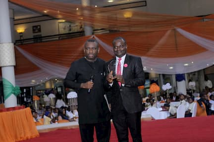 DR GEORGE AKPAN PRESENTING AN AWARD ON BEHALF OF THE SUBJECT SPONSOR DELTA AFRIK TO THE 2ND PLACE CHEMISTRY WINNER GODWIN JOHNSON AKPAN
