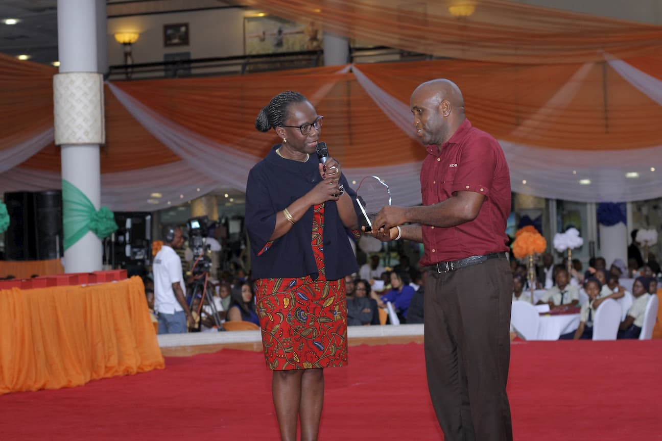DR. MYMA BELLO-OSAGIE PRESENTING AN AWARD TO THE 1ST PLACE WINNER HISTORY UDUAK AMOS AKPANOWO