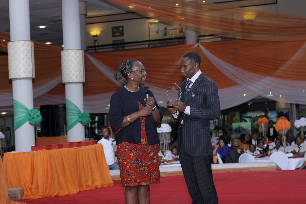 DR MYMA BELO OSAGIE PRESENTING AN AWARD TO THE 2ND PLACE WINNER ECONOMICS ANIEKAN OKONAH UDOH