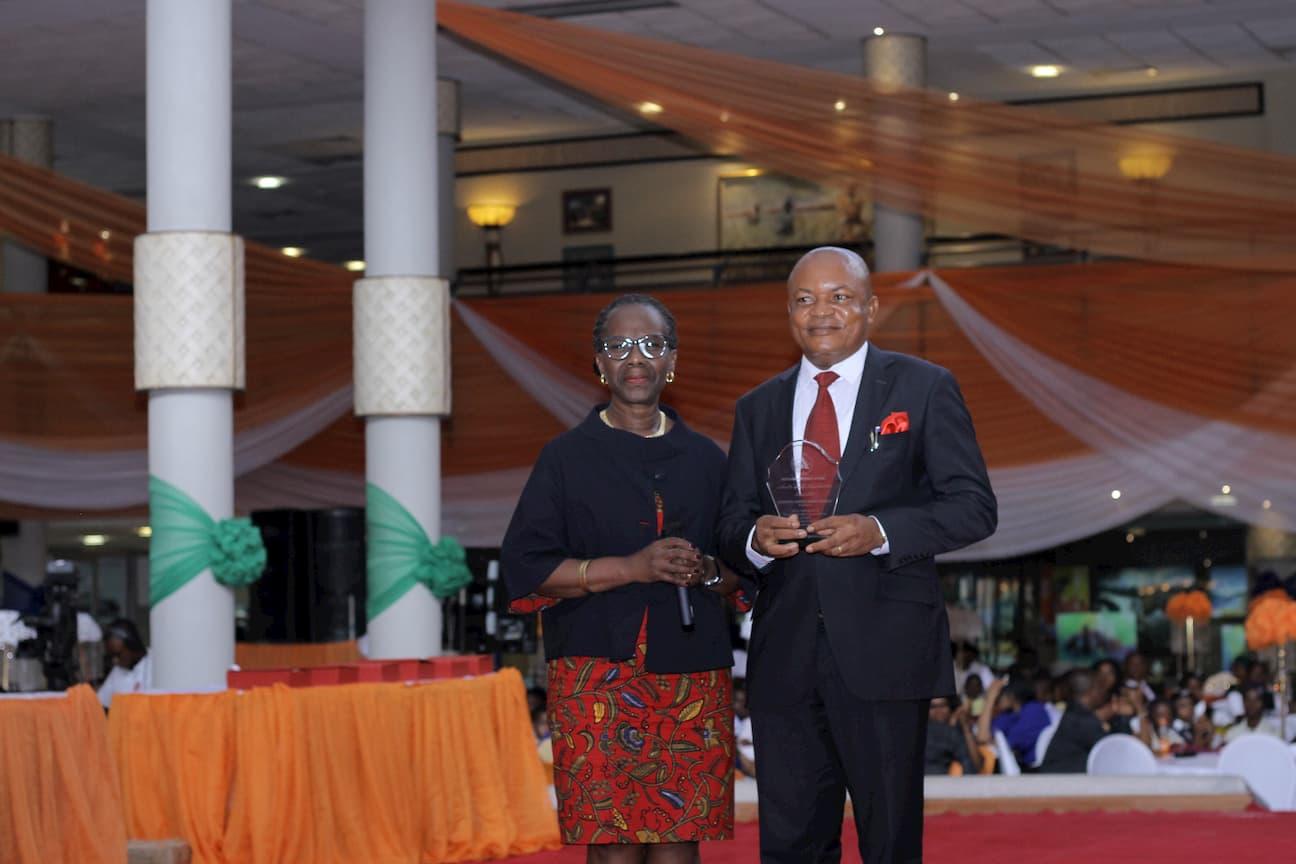 DR MYMA BELO-OSAGIE PRESENTING AN AWARD TO THE 2ND PLACE WINNER HISTORY GODWIN C. IYAKNDUE