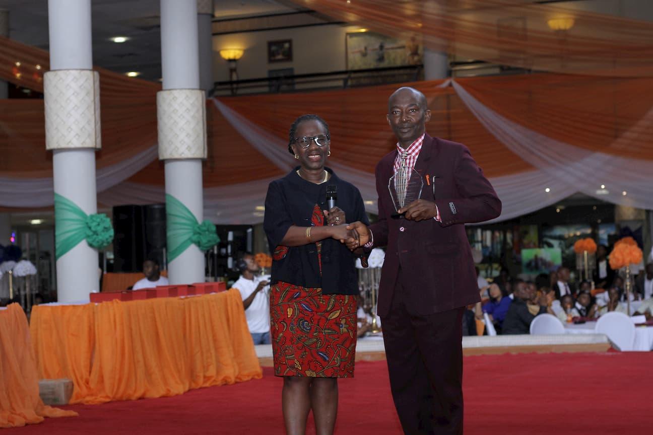 DR MYMA BELO-OSAGIE PRESENTING AN AWARD TO THE 3RD OLACE WINNER ECONOMICS UWEM OKON AKPAKPAN