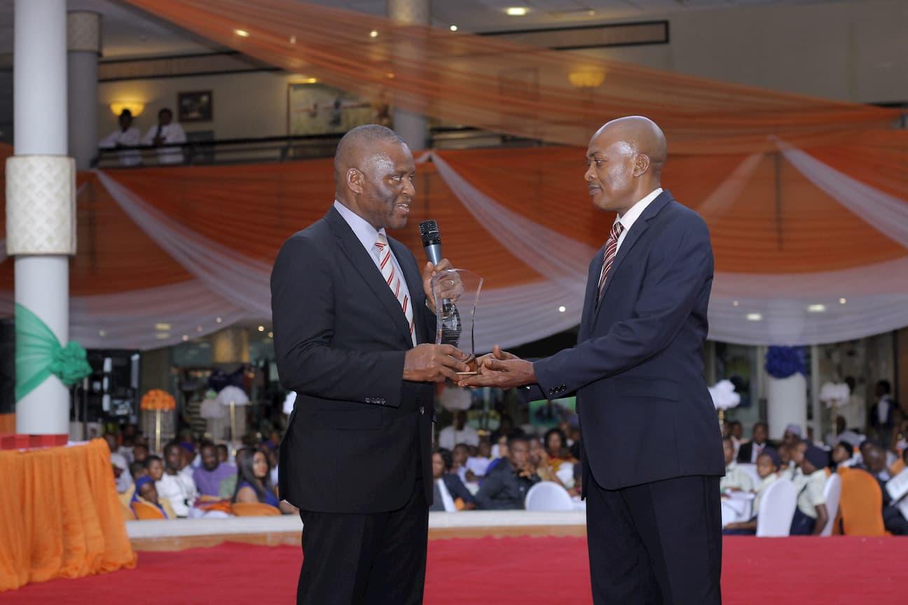 MR. BASSEY UMOH PRESENTING AN AWARD TO THE GRAND MENTOR AWARD WINNER ENGLISH MY SILVANUS GEORGE