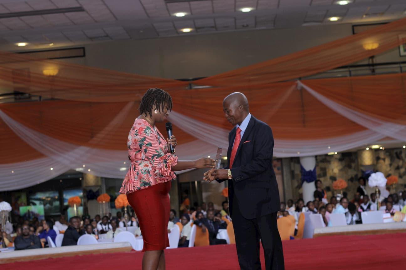 MRS NKOYO ETUK PRESENTING AN AWARD ON BEHALF OF THE SPONSOR ENGR UWEM OKOKO TO THE 3RD PLACE WINNER FOR BIOLOGY MICHAEL UDO