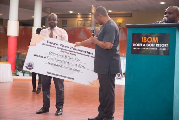Mr. Iniodu Akpan presenting the award unbehalf of the sponsor Mr. Ken Etim  to 1st Prize Winner History Ofonime Udo of Com. Sec Sch Mbak Etoi