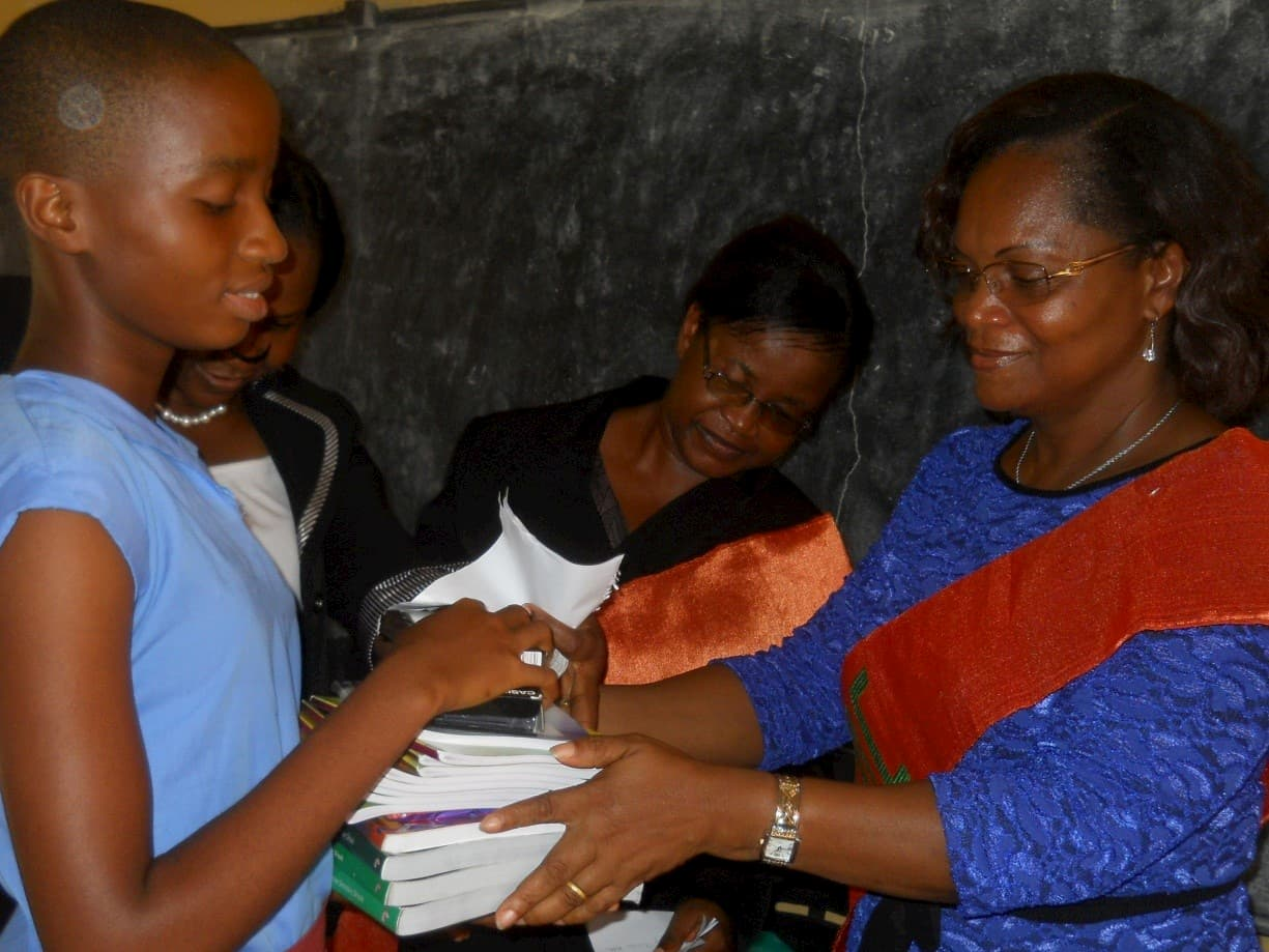 Dr. Stella Nwosu presenting a set of tect books to best Physics Students in SS1